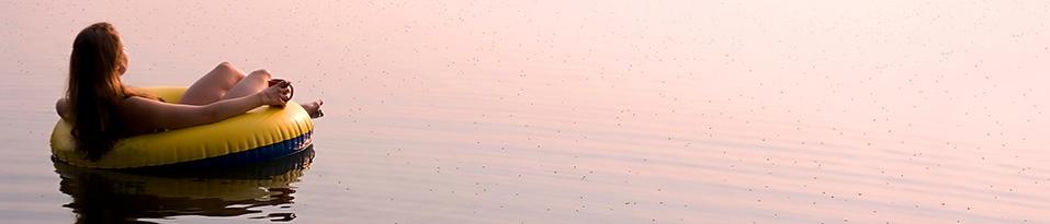 Frau auf See im Sonnenuntergang